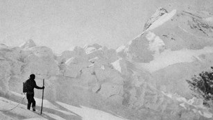 a historic photo of a man standing on a snow overed mountain