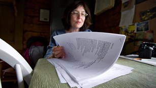 a woman shifts through a stack of papers on a desk
