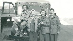 four women standing in front of a bus on a dirt road