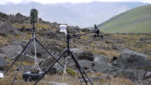 two tripods holding sound equipment sit on a rocky hillside