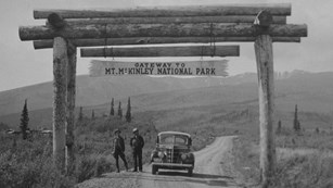 two people stand next to a car under a sign for Mt. McKinley National Park