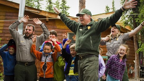 A group of campers and rangers wave their arms above their heads