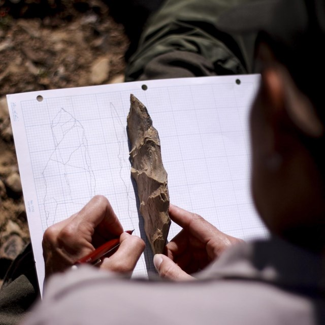 a person draws an archeological artifact