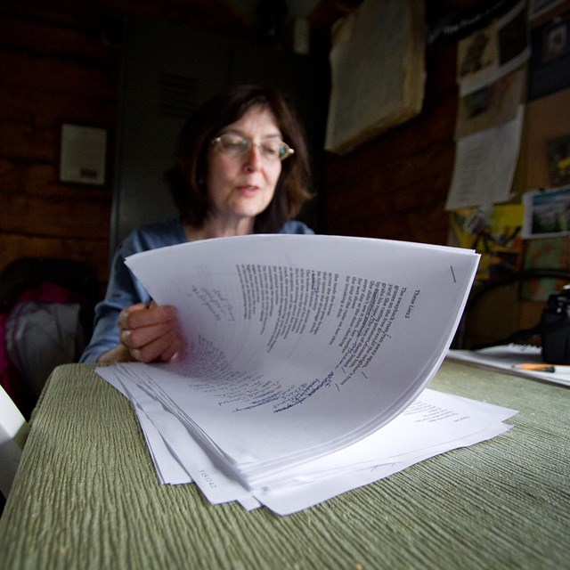 a woman sitting at a table reads through a stack of papers