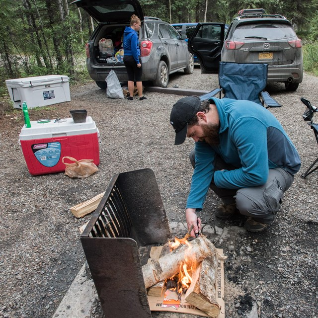 man kindling a fire while a woman unloads camping equipment from a car