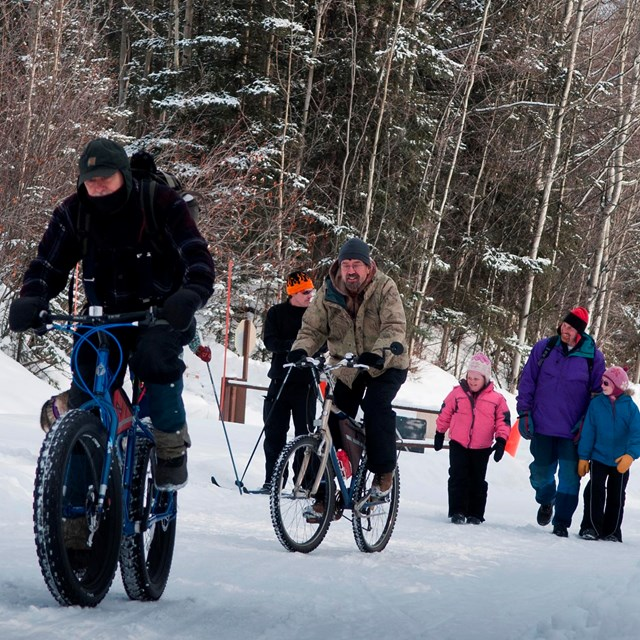 several people riding fat tire bikes while others walk on a snowy road