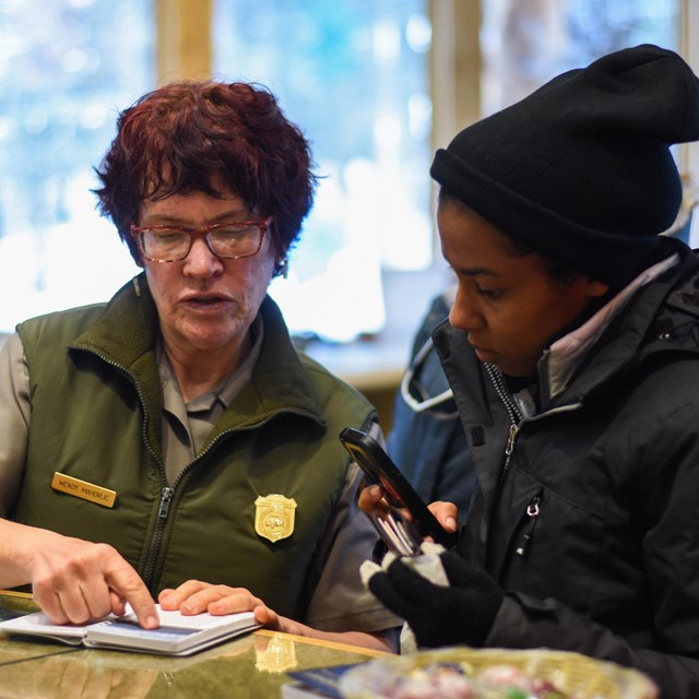 a park ranger speaks to a young woman at a desk