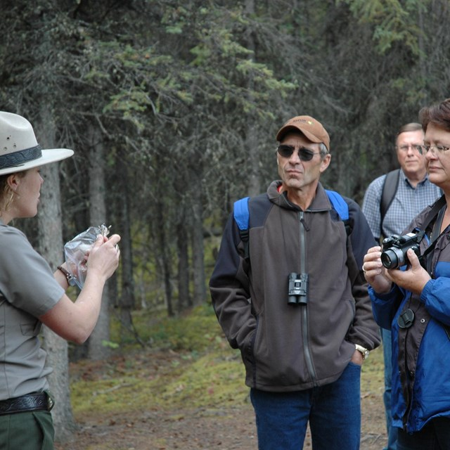 a female ranger shows a group of people an object on a trail