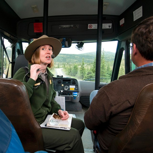 a ranger sitting on a bus speaking in a microphone to other passengers