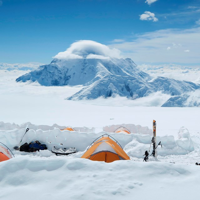 snowy, mountainous landscape with numerous people and tents in the distance