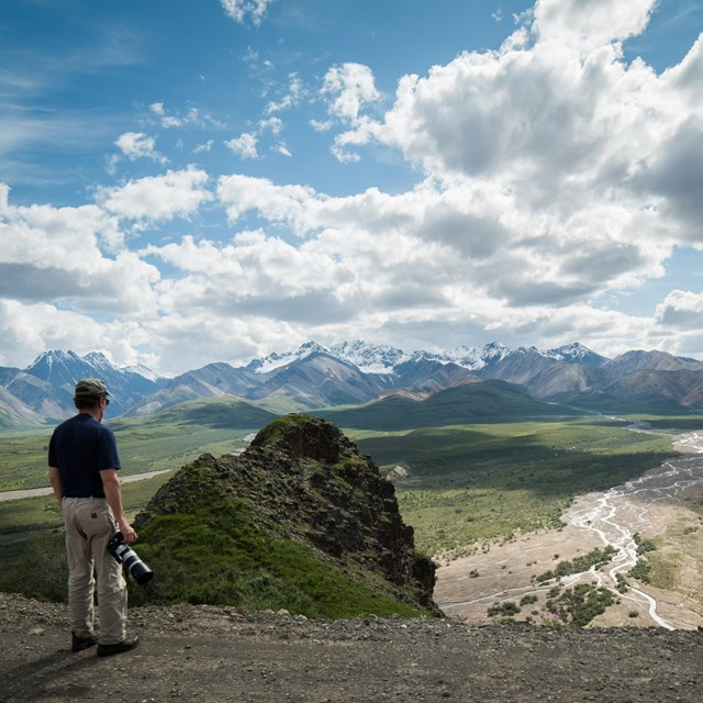 a man standing at a scenic overlook above a wide green plain leading up to distant mountains