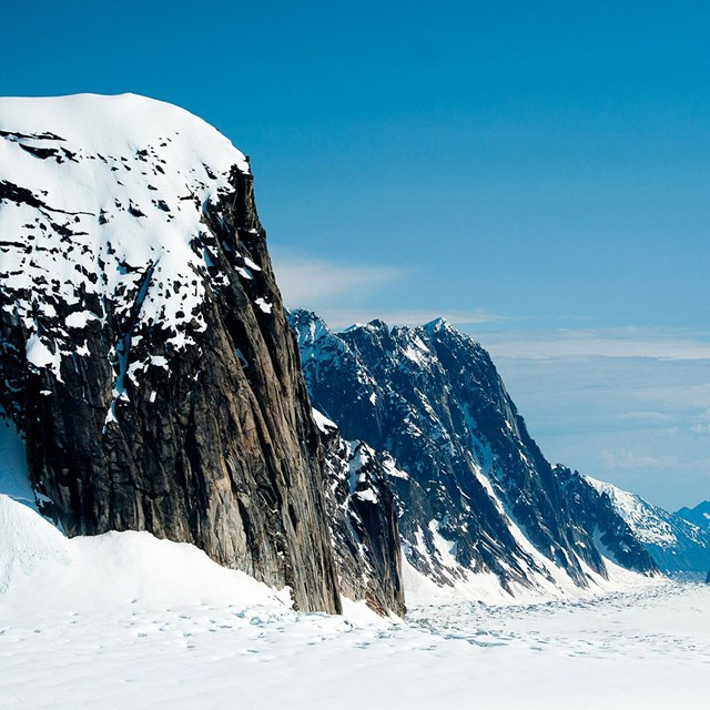 Snow covered rocky ridges loom over a glacier
