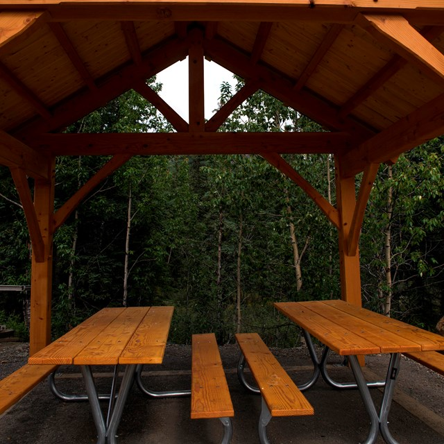 picnic tables under a large wooden structure