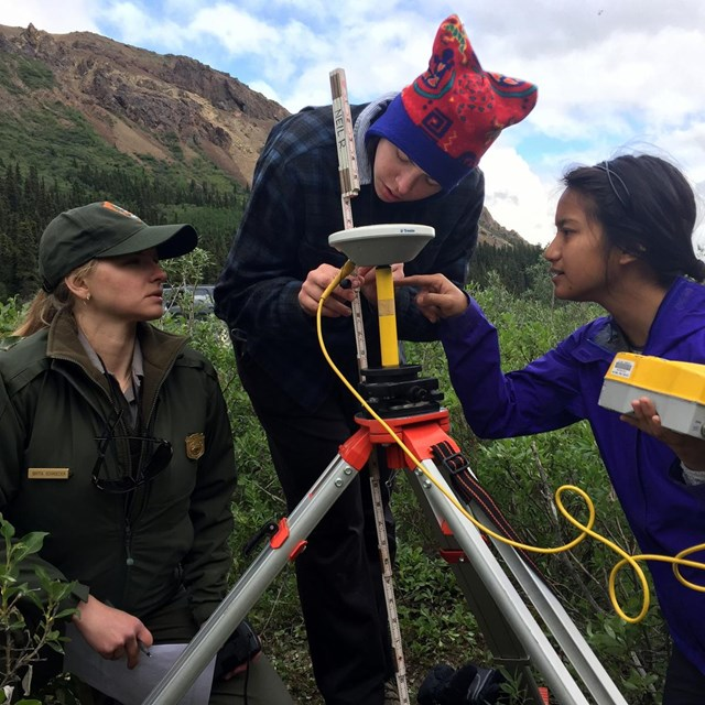 campers work with a ranger to set a survey station