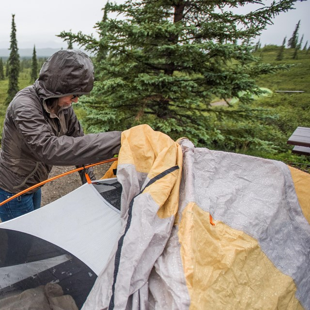 woman putting a rain fly on a tent