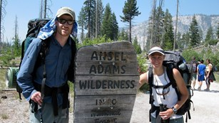 Wilderness backpackers pose near Ansel Adams Wilderness sign.
