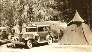 A historic photo from 1935 depicts a car camped beside a tent in the campground.