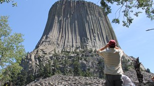 man with binoculars in foreground, Devils Tower in background