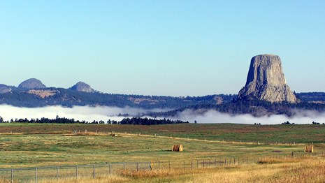 Devils Tower and the Little Missouri Buttes rise above the fog.