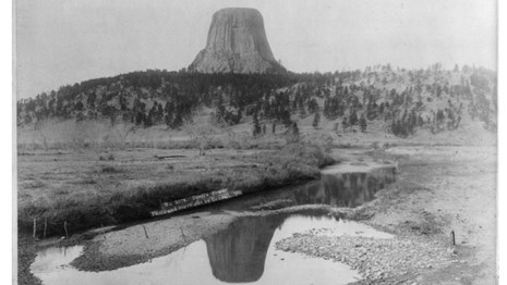 Historic photo of Devils Tower with river in foreground