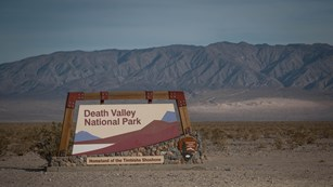 Death Valley National Park entrance sign in a desert landscape.