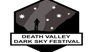 Death Valley Dark Sky logo with a person standing looking at a star-filled sky.