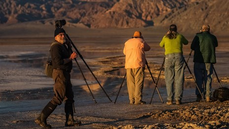 four people taking pictures of mountains and salt flats as a man smiles at the camera