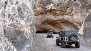 Jeeps drive through the Titus Canyon Narrows