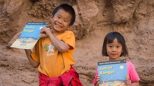 two children holding booklets