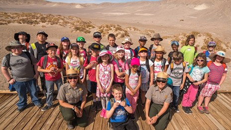 Rangers and students pose for a picture on a boardwalk.