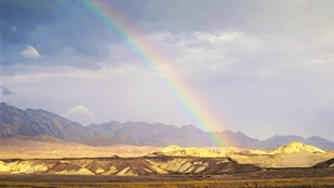 A rainbow reaches down to shimmering desert mountains.