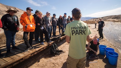 Volunteers stand along a boardwalk facing an employee giving directions.