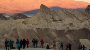 A group of photographers stand on a ridge photographing the sunrise on the desert hills.