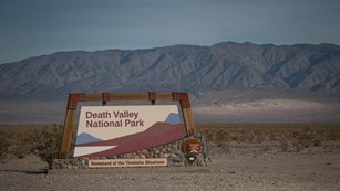 Death Valley National Park sign with distant, highly-eroded, brown desert mountains.