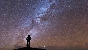 A ranger silhouette stands in front of a milky way, starry backdrop.