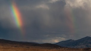 A double rainbow in a clouded sky, above a stark desert landscape.