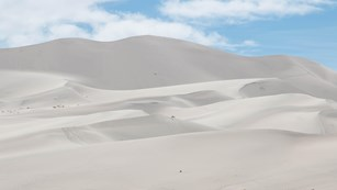 A large towering sand dune under a blue sky with scattered clouds.