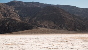 A vast salt flat of polygon shapes leads to an alluvial fan at the base of a desert mountain.