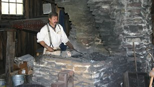 Blacksmith at work at the furnace