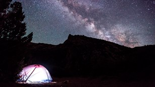 lighted tent underneath a starr filled night sky