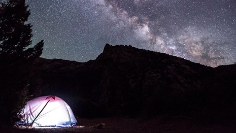 A glowing tent sitting beside a tree. In the background is a sharp ridgeline beneath a starry sky.