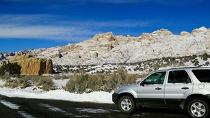 Silver vehicle sitting on road with rocky mountains covered in snow in the background
