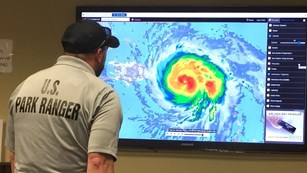 Park ranger looking at radar image of hurricane on television