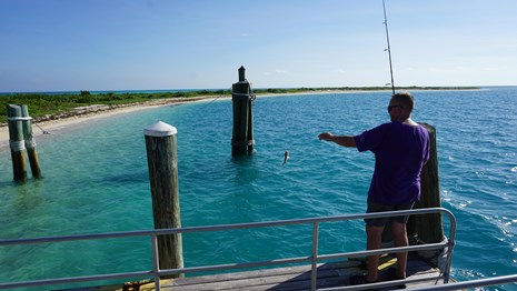 A man standing on a dock by the ocean, holding a fishing pole with a fish on the line.