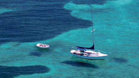 A large sail boat and a small boat floating on clear water