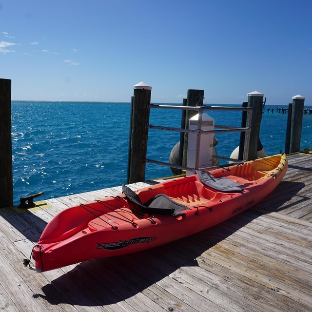 A long orange and yellow kayak vessel resting on a wooden dock beside a blue ocean and blue sky