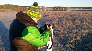 Woman takes photos in the chilly winter dawn.