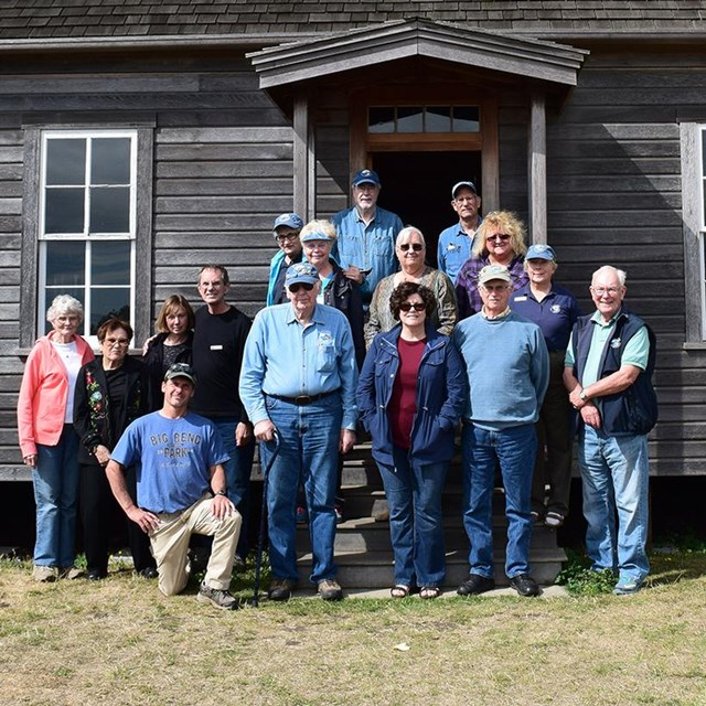 group of volunteers stand on the front porch of the historic Jacob Ebey House.