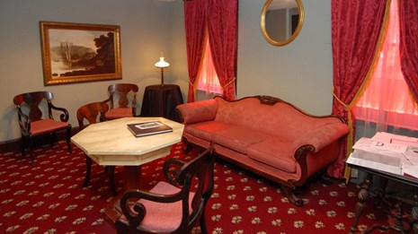 Color photo of a room furnished with red carpet, red sofa, and marble topped table.