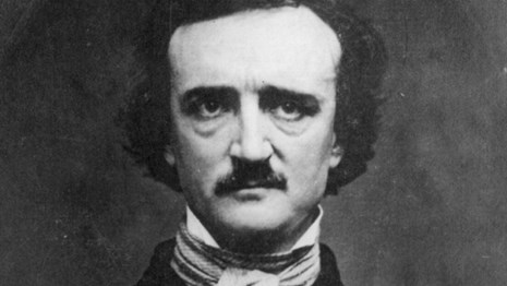 Black and white photo of a man with dark hair, high forehead, and bushy mustache and eyebrows.